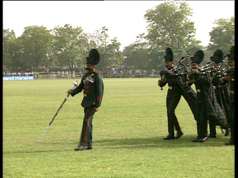 Soldiers in traditional military uniform play bagpipes and march across polo field Royal Tour of India; Feb 92