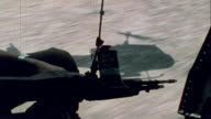 Soldiers in UH1B helicopter flying over Ba Lai River above embattled PBR gunboats speaking via radio with command station approaching combat zone and...