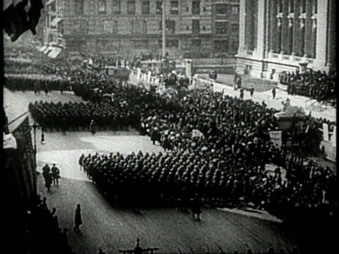 soldiers marching in formation through city street / crowd of women cheering / soldiers marching past crowd waving American flags