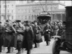 B/W 1918 soldiers marching in street past trolleys / Germany / documentary