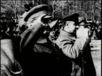 Soldiers marching / Trotsky salutes the troops / Stalin speaks at a podium / Cars driving in front of a city skyline / People walk in the snow /...
