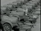 US TRANSPORT US Soldiers marking fuel tanks labeled 'Chunking' US Light tanks parked in line one moving out of area another moving onto railroad...