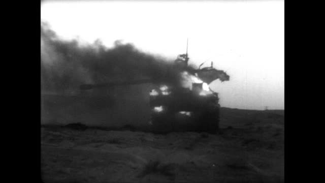Soldiers mill about base camp in the Suez area during Six Day War / soldier in tank looks through binoculars / Israeli tank in flames / CU burned out...