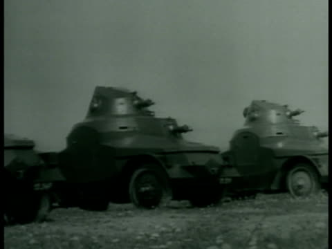 Soldiers moving in open cars some pulling artillery WS Tanks moving in line on open field Camouflaged larger tanks moving in formation pre war WWII