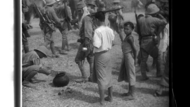 Soldiers of the Imperial Japanese Army receive water and encouragement from civilians as they advance past supply convoys and armor units before they...