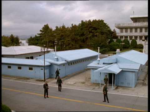Soldiers patrol area around blue buildings which are built on actual border of North and South Korea