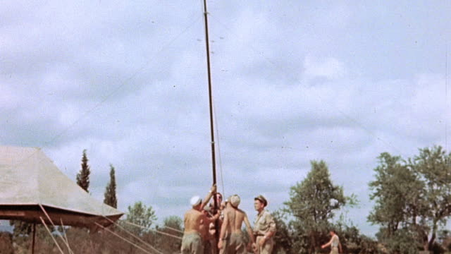 Soldiers planting flagpole and raising American flag / Corsica France
