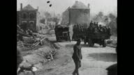 MONTAGE Soldiers pushing truck through mud, trucks carrying soldiers through town and along country lane with dust flying, mortar firing, and driver painting slogan atop delivery van / United Kingdom