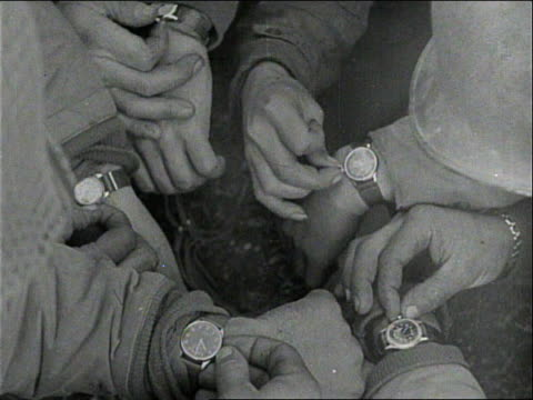 soldiers set their watches / a soldier wearing his watch