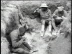WWI soldiers sitting and eating in trenches