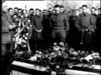 Soldiers standing around a coffin at a military funeral while one man speaks and then salutes deceased / France