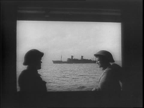 Soldiers talking aboard ship large transport ship in background / ocean liner at sea / montage of troops marching and unloading supplies at a port /...