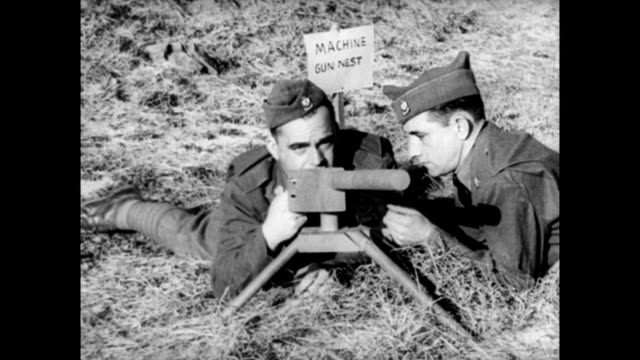 US soldiers training for war with makeshift fake equipment such as wooden machine guns and trucks that have banners saying 'tank' / actual machine...