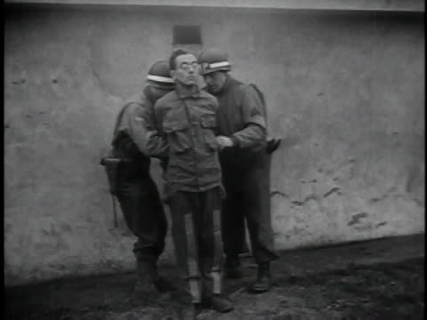 Soldiers tying up convicted criminals to posts in front of wall / firing squad getting ready / over the shoulders of firing squad