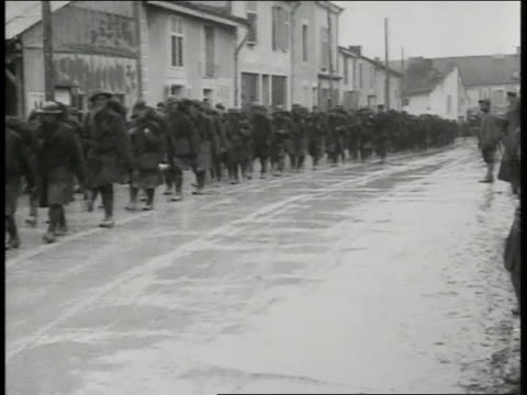 REPRISAL Soldiers waiting in trench EUROPE US WWI Soldiers walking in line on wet muddy street through town Trucks traveling on muddy road US...