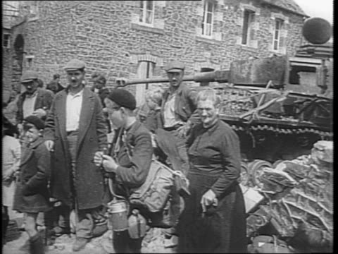 Soldiers walk through building debris / montage of French refugees staring at ruins / US troops ride in a military vehicle through Saint Lo / A tank...