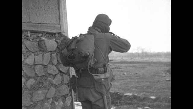 Soldiers walking along top of ridge past smoking ruin / soldier walking along railroad tracks next to wall / two shots of soldier firing rifle from...