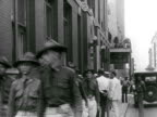 Soldiers walking down sidewalk WS Soldiers turning corner w/ truck passing FG VS Soldiers patrolling inside window sitting w/ radio sitting in window...