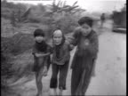 Soldiers walking on path thru field with fire in background during Vietnam War / three scared and hungry Vietnamese refugees walking from field to...