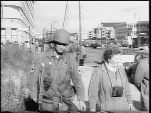US soldiers walking past senior couple on sidewalk / Berlin Germany / newsreel