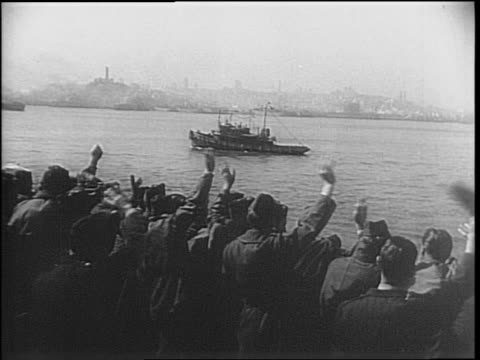 Soldiers wave from boat close to land / men march down gangplank / civilians greet and celebrate their return