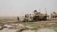 Soldiers with the Afghan National Army recover a tactical vehicle after it becomes stuck in a muddy field while on patrol with soldiers from the US...