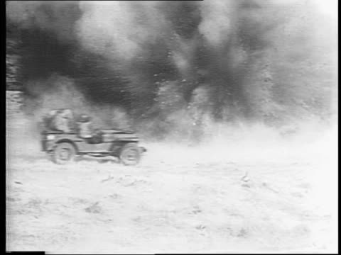 Soldies run from glider and jump into jeeps driving across a field as bombs explode near them / soldiers with guns running through field and taking...