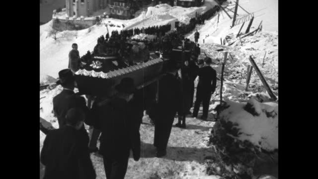 VS solemn altar boy with lit candle and long line of villagers pallbearers with coffin walking up incline approaching St Nicholas Church in valley...