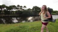 Solo Female Backpacker Walking by River