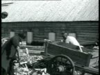 Solovki labor camp prisoners walking carrying brooms and shovels on shoulders loading wood shavings women doing laundry and stacking bricks /...
