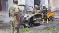 Somali firefighters work to burning vehicles while Somali security officials inspect the scene of a car bomb explosion near a police station in the...