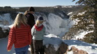 WS Some child's and woman looking snowy forest landscape with frozen waterfall / Yellowstone National Park, Wyoming, United