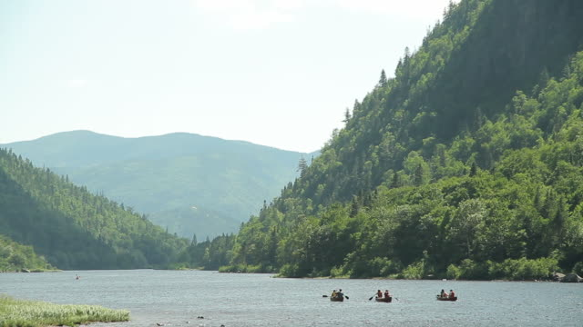Some people are canoeing on the river near the mountains