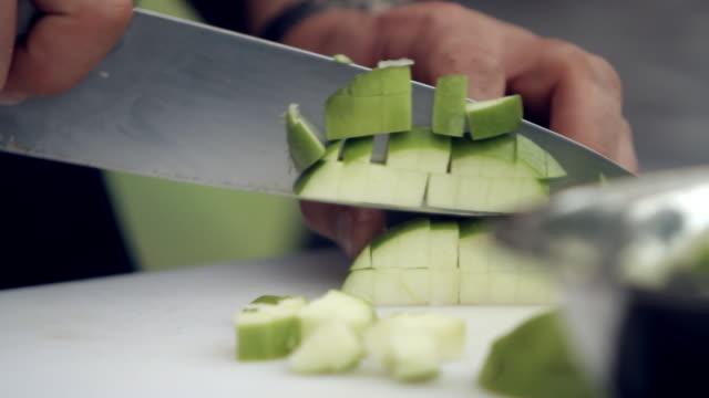Someone cuts green apples