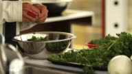 Someone cuts parsley with his hands in a bowl aluminum