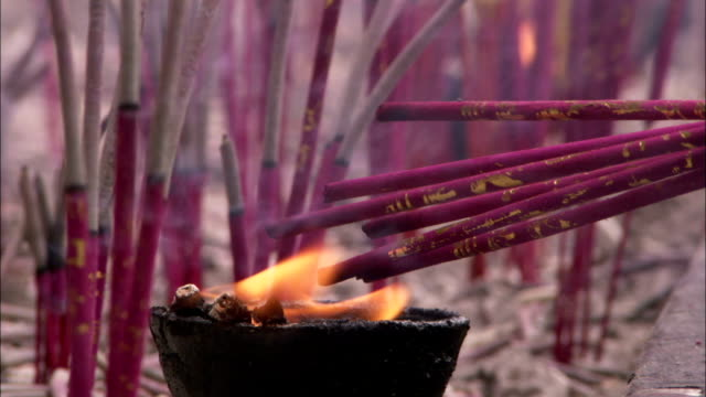 Someone lights incense sticks with a candle. Available in HD.