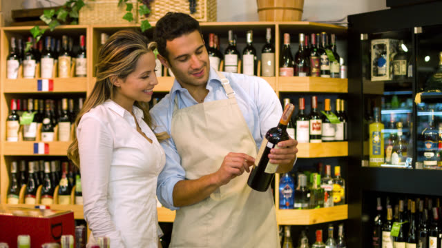 Sommelier helping woman at the supermarket buying wine