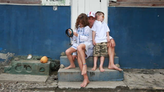 Son and daughter sit on fathers lap outside a Spanish police station on the beach and daughter holds fishing line.