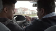 Son learning to drive car with father