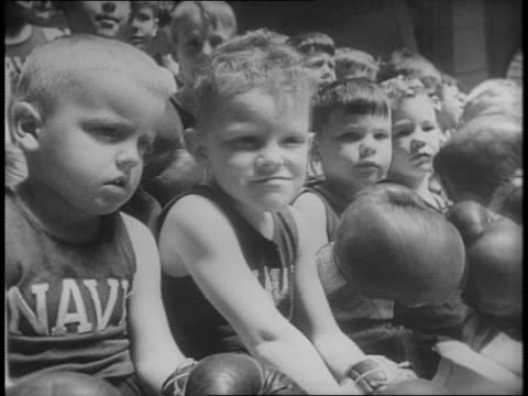 Sons and young boys of Naval Academy officers sit on bleachers shaking boxing gloves / two little boys fight in the ring in front of the audience...