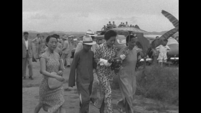 VS Soong MeiLing deplanes and is greeted by a United States military officer she walks quickly to meet sister Soong ChingLing under a parasol and...