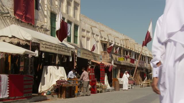 WS Souq Waqif with market stalls and Qatari flags on building / Doha, Qatar