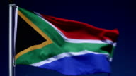 4K: South African Flag on Flagpole in front of Blue Sky outdoors (South Africa)