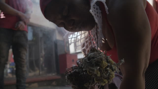 South African woman burns herbs for ritual, close up