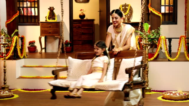 South indian woman swinging her daughter on porch swing, Delhi, India