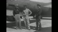 Soviet airmen and US officer stand in front of US military airplane / 2shot Russians smile pan to smiling US airman