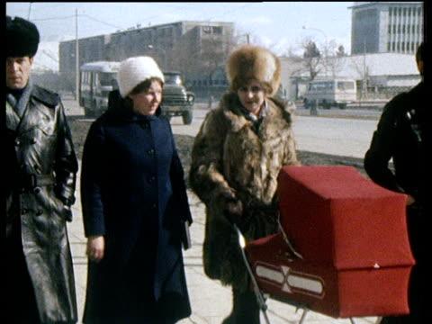 Soviet family resident in Kabul push pram past camera following Soviet invasion of Afghanistan 1979