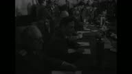 Soviet Marshal Georgy Zhukov and other Allied officers enter conference room where surrender will be signed / officers gathered around conference...
