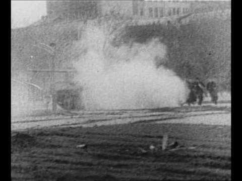 Soviet tank on Budapest street / CU hand prepares Molotov cocktail / rear shot man lights Molotov cocktail throws it over wall / smoke from tear gas...