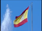 Spanish flag flapping in the wind against blue skies next to the spray of a fountain in Seville.